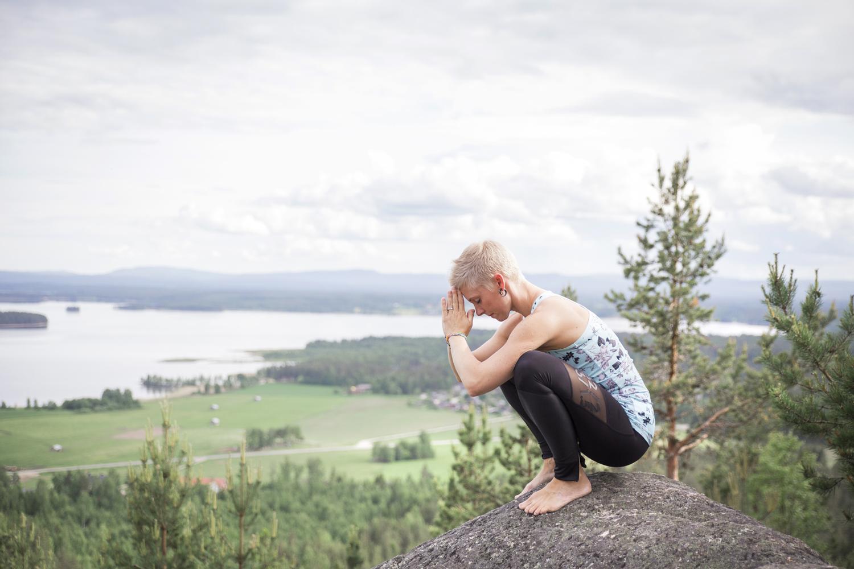 Tjej som sitter på huk med hopknäppta händer mot pannan på ett berg med utsikt över sjö och skog