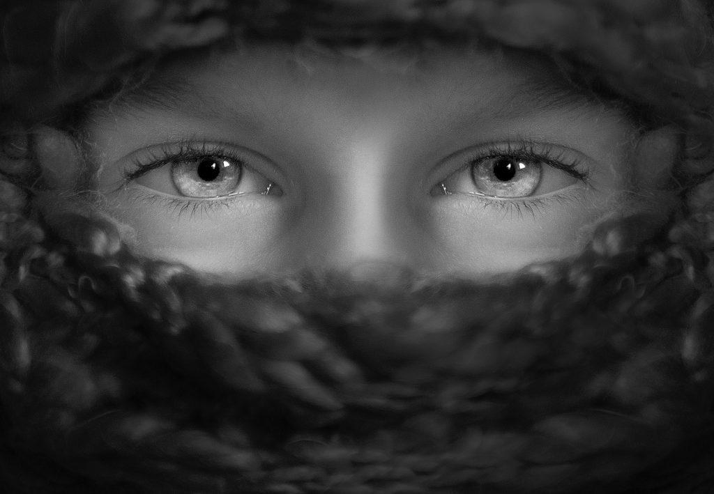 grå bild med person som har täckt ansikte och endast ögonen syns